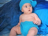 dziecko w niebieskiej czapce na niebieskim kocu