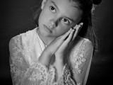 dziewczynka ze złożonymi dłońmi przy policzku