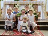 siedzące dzieci przy ołtarzu na komunii świętej