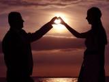 dłonie złożone w kształt serca na tle słońca